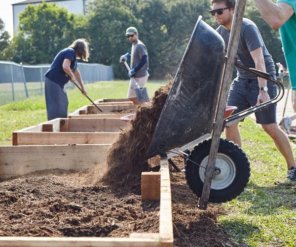 Volunteers fill community garden beds at Fossil Group