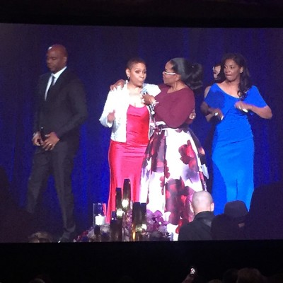 Oprah greets Janiece Evans Page and Steve Evans of Fossil Group on stage at Minnie's Food Pantry Gala 2018
