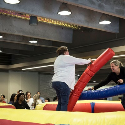 Two Fossil Group employees play jousting game at annual spring fest