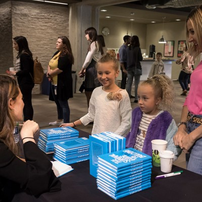 Aija Mayrock shares her best selling book with students at an IDG event at Fossil Group in Texas
